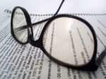 Image of glasses and a report for an article about How To Get the Most From Your Spend Analysis Reports.