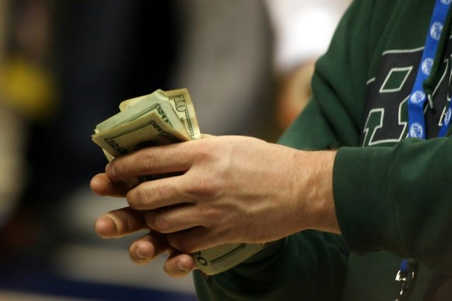 Image of a man holding money for an article about What is eTendering and Its Process.